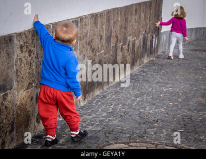 Little kids - brother and sister walking along the home wall in Spain - Stockfoto