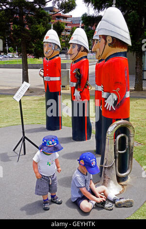 Military Brass Band bollards, by artist Jan Mitchell, with small boys playing on waterfront park in Geelong, Victoria, - Stock Photo