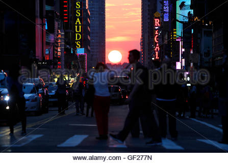 People stop to view the sunset at 42nd Street during the biannual occurrence named 'Manhattanhenge' in New York, - Stock Photo