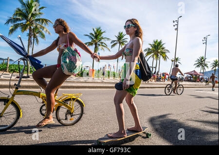 RIO DE JANEIRO - MARCH 6, 2016: Young Brazilian woman on bicycle tows a friend on skateboard on the Ipanema beachfront - Stock Photo