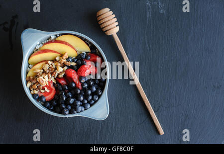 Healthy breakfast in blue bowl with fruit toppings and honey stick. Breakfast with cottage cheese, honey, peaches, - Stock Photo