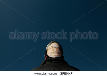 A man wearing a masque with a photo of Juan Luis Cebrian,  CEO of Spanish media conglomerate Prisa, takes part in - Stock Photo
