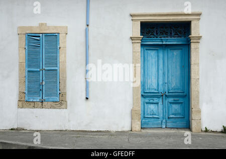 Photo of typical Cypriot old aged white building with bright blue wooden door ,window with closed shutters and rainwater - Stock Photo