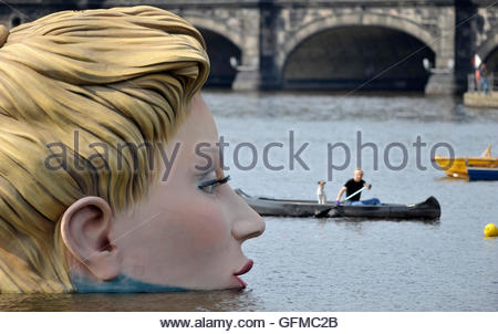 A man and his dog in a canoe paddle around a sculpture of a mermaid at the 'Alster' lake in Hamburg August 3, 2011. - Stock Photo