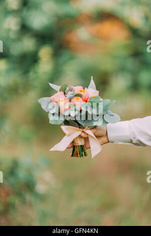 Wedding. Male hand holding a bouquet of pink flowers and greenery in green garden - Stock Photo
