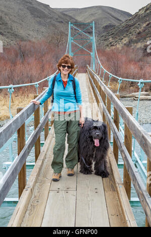 Woman and Newfoundland dog on suspension bridge over the Yakima River at Umtanum - Stock Photo