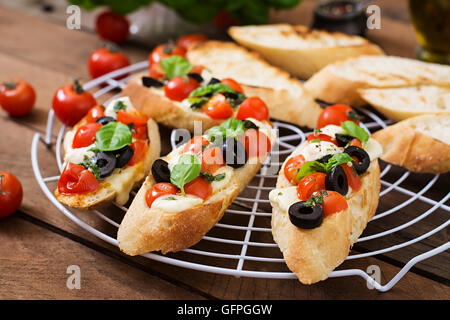 Bruschetta with tomatoes, mozzarella, olives and basil pesto - Stock ...