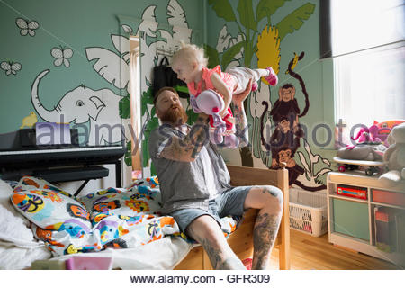 Playful father flying daughter in bedroom - Stockfoto