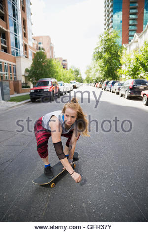 Cool young woman skateboarding on urban street - Stock Photo