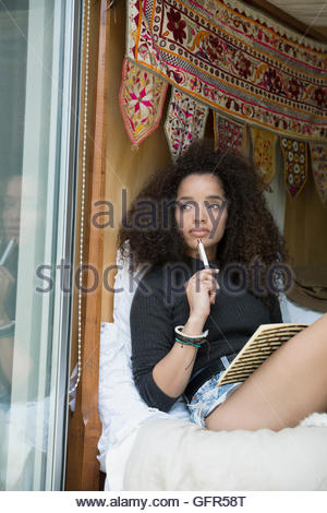 Pensive young woman writing in journal at bedroom window - Stock Photo