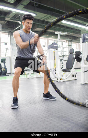 Young Chinese man exercising with battling rope at gym - Stock Photo