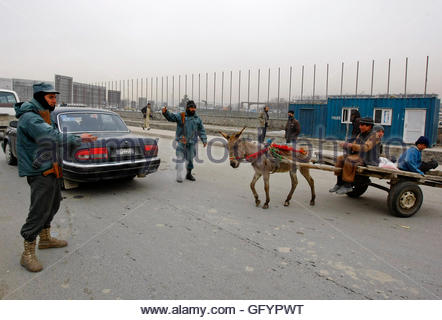 Afghan policemen keep watch as donkey cart pass by a check point in Kabul February 26, 2012. Afghanistan's interior - Stock Photo