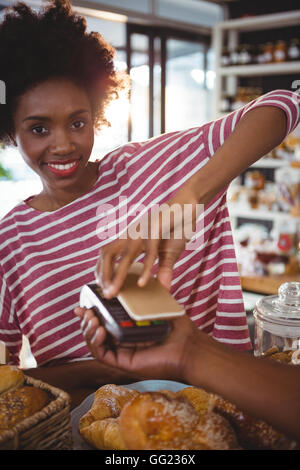 Smiling woman paying bill through smartphone using nfc technology - Stock Photo