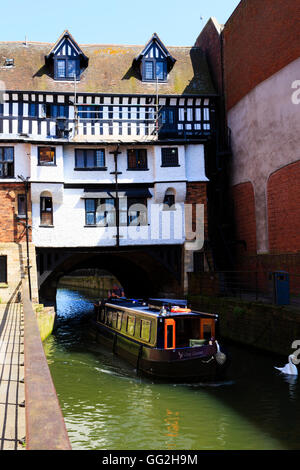 A canal barge exits from under the Elizabethan High Bridge, the oldest in England, on the River Witham, Lincoln, - Stock Photo