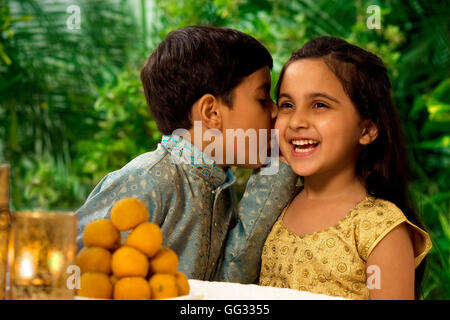 Boy whispering in his sisters ear - Stock Photo