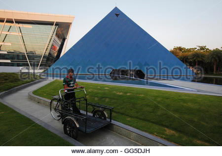 A man pushing a tricycle cart walks in front of a pyramid-shaped building made out of glass in the Infosys campus - Stockfoto
