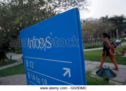 An employees walks past a signage board in the Infosys campus at the Electronics City IT district in Bangalore, - Stock Photo
