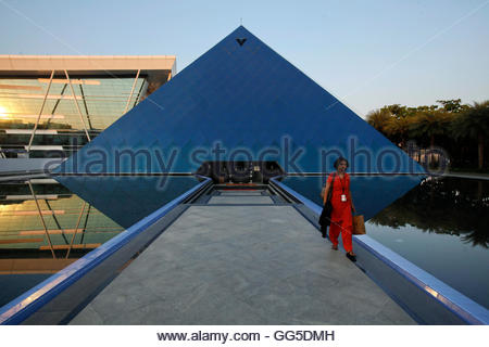 An employee walks out of an iconic pyramid-shaped building made out of glass in the Infosys campus at Electronics - Stockfoto