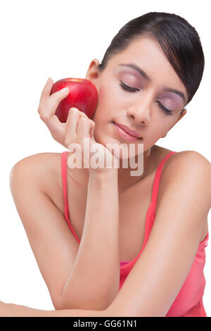 Close-up of young woman holding apple with eyes closed over white background - Stock Photo