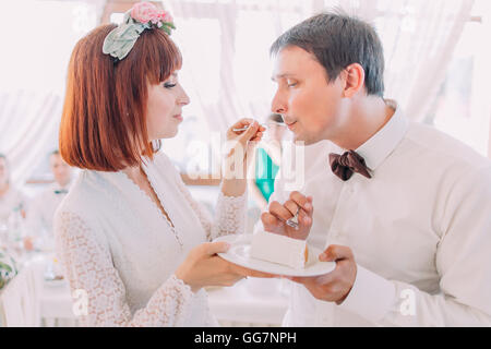 Beautiful young bride feeding wedding cake to groom in light restaurant interior - Stockfoto