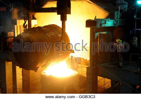 Workers look at a ladle pouring molten iron into a container at a steel plant in Hangzhou, Zhejiang province May - Stock Photo