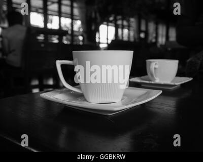 White cup of coffee on the wooden table in cafe restaurant . Black and White picture - Stock Photo