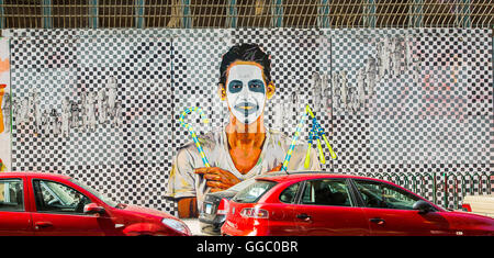 Egypt, Cairo, graffiti of the Egyptian revolution . Young man with a clown mask in front of a big chessboard. - Stock Photo