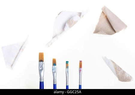 cardboard fragments and four painting brushes with dry color traces on them - Stock Photo