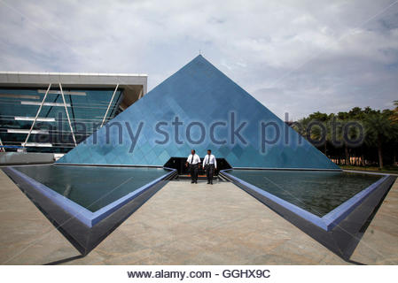 Employees walk in front of a pyramid-shaped building at the Infosys campus in the Electronic City area of Bangalore - Stockfoto