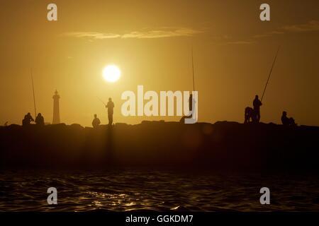 Fishermen on a pier in Rabat at sunset, Morocco - Stockfoto