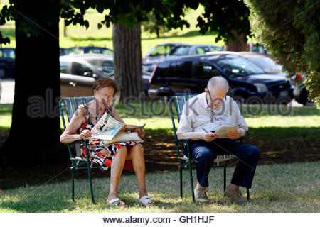 A couple relaxes under trees in the shade at a public park during a hot summer day in Rome August 3, 2012. The temperature - Stock Photo