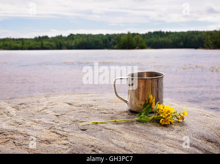Stainless steel mug on stone near water on nature background - Stockfoto