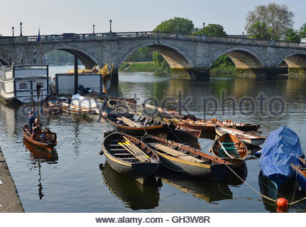 A couple row out on their boat in front of the moored Diamond Jubilee Royal barge at Richmond in south west London - Stock Photo