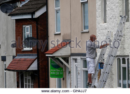 A man paints a house near a property for sale in Burton Upon Trent August 13, 2013. British house prices are rising - Stock Photo