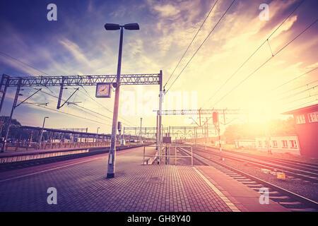 Vintage stylized railway station platform at sunset, travel concept. - Stock Photo