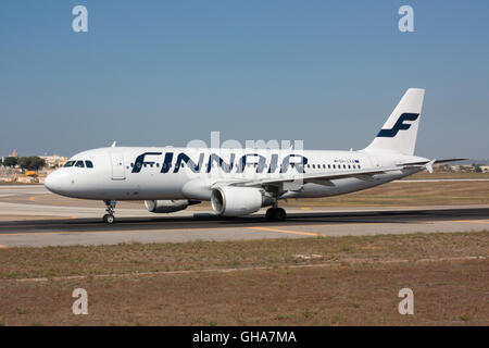Air travel. Finnair Airbus A320 taxiing for departure from Malta - Stock Photo