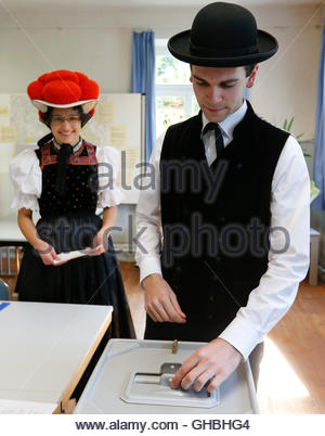 Traditionally dressed Christoph Woehrle casts his ballot next to Gerlinde Moser in the general election (Bundestagswahl) - Stock Photo