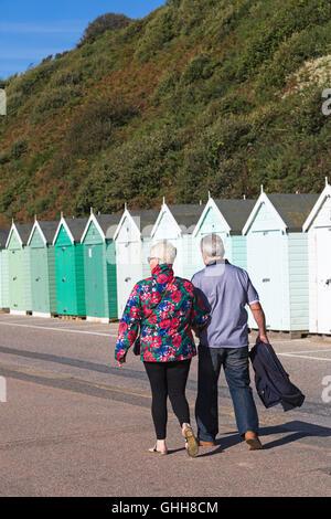 Bournemouth, Dorset, UK. 28 September 2016. Couple walking past shades of green beach huts along promenade of various - Stock Photo