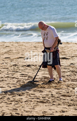 Bournemouth, Dorset, UK. 28 September 2016. Man with metal detector at Bournemouth beach in September wearing humourous - Stock Photo