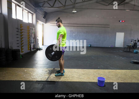 Athlete lifting a barbell in gym - Stock Photo