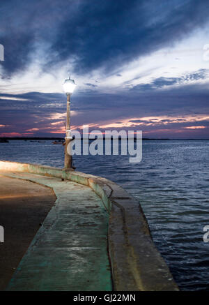 After Sunset on Sea Wall at Rio Lagartos. A street lamp glows with a sunset sky beyond as a shrimp fisher hangs - Stock Photo