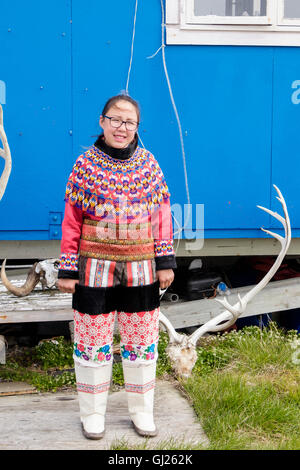 Inuk girl wearing colourful traditional costume standing posing outside her house. Itilleq, Qeqqata, Western Greenland. - Stock Photo