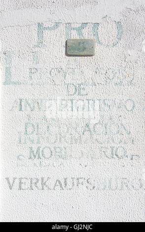 Printed unlegible words in various languages on white roughcast wall on August 5 in Port Andratx, Mallorca, Spain. - Stock Photo