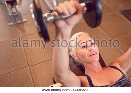 Woman working out with dumbbells in gym - Stockfoto