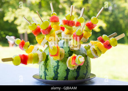 Watermelon decorated with colorful fruit skewers, with shallow depth of field. - Stock Photo