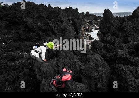 A woman climbs on volcanic rocks near a tidal pool, Big Island, Hawaii - Stockfoto