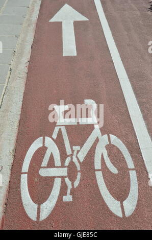 Bicycle sign and arrow on red lanes road. - Stock Photo
