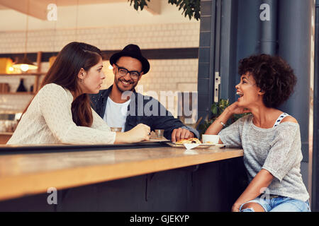 Portrait of a young group of friends talking in a cafe. Young man and women sitting at cafe table and talking. - Stock Photo
