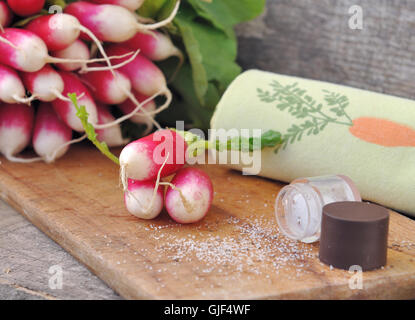 fresh radishes on board kitchen with salt - Stock Photo