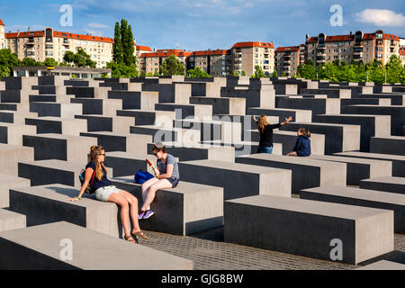 Tourists sitting on the concrete blocks of the Holocaust Memorial  to the murdered Jews of Europe, Berlin, Germany. - Stock Photo